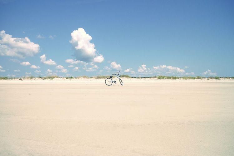 Man skateboarding on sand against sky