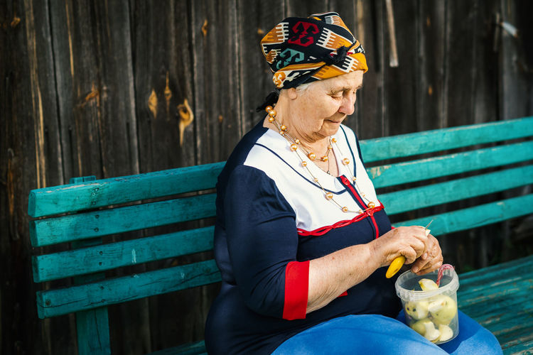 Senior woman peeling apple while sitting on bench at park