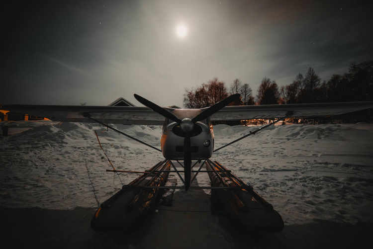 Biplane against sky at night during winter