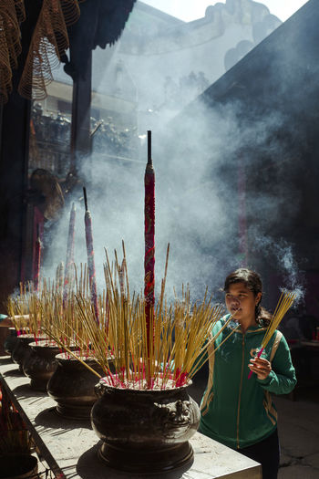 Shot at Thien Hau Temple, Saigon, Vietnam. Adult Ash Burning Cultures Day Hope Incense Indoors  One Person People Place Of Worship Real People Religion Shrine Sky Smoke - Physical Structure Smoking - Activity Spirituality Standing Young Adult