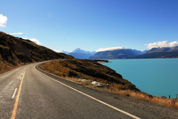 Empty road by lake pukaki against sky