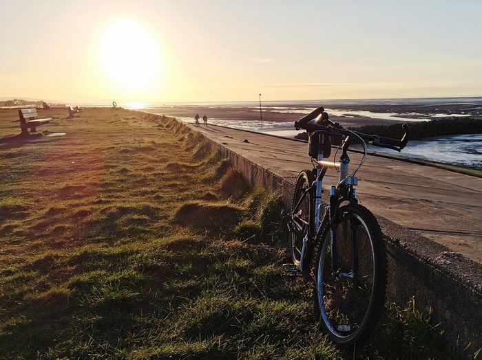 Bicycle on field by sea against sky during sunset