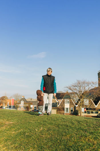 Grandfather Standing With Granddaughter On Grassy Field Against Blue Sky
