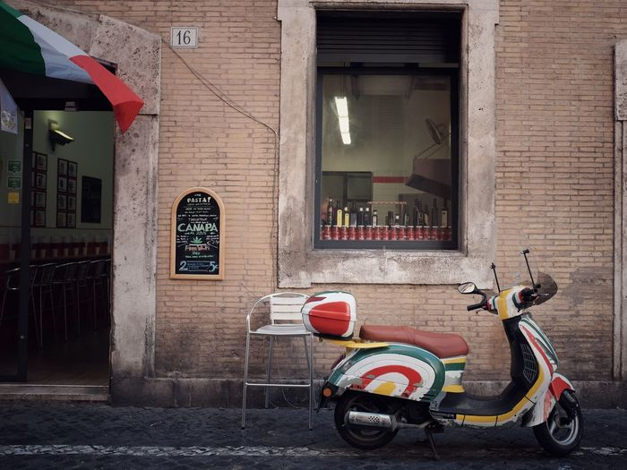 When in Rome Rome Streetphotography Street Flag Italy Still Life Vespa Building Exterior Architecture Built Structure Transportation City Mode Of Transportation Day Building Brick Wall Scooter Wall - Building Feature Brick