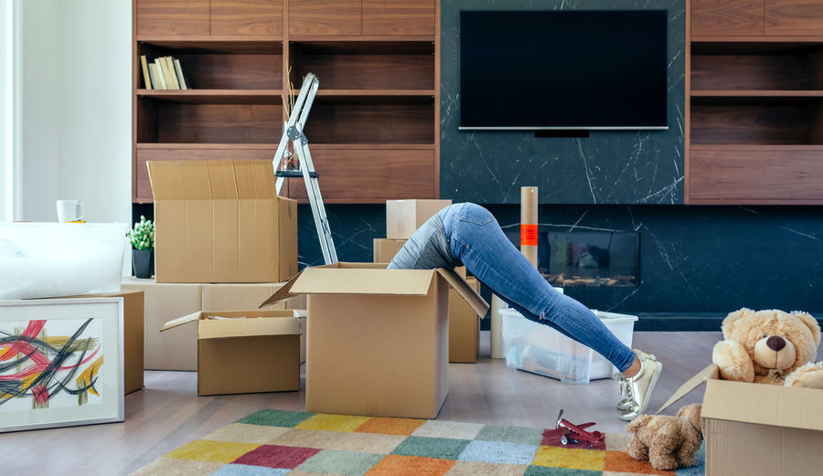 Young woman inside a box while preparing the move Family Fun Happiness Happy Horizontal Moving Unpacking Apartment Boxes Cardboard Home Interior House Indoors  Inside Legs Lifestyles Living Room Looking New Home One Person Packing Placing Real People Relocating Unrecognizable Person