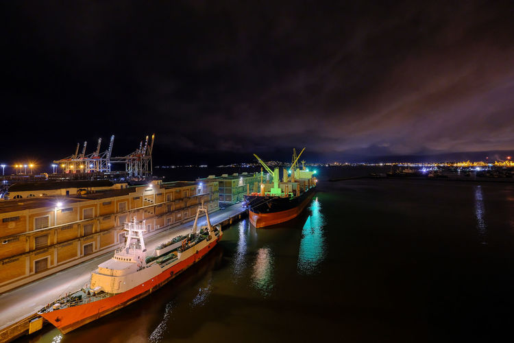 Panoramic view of illuminated harbor by sea against sky at night