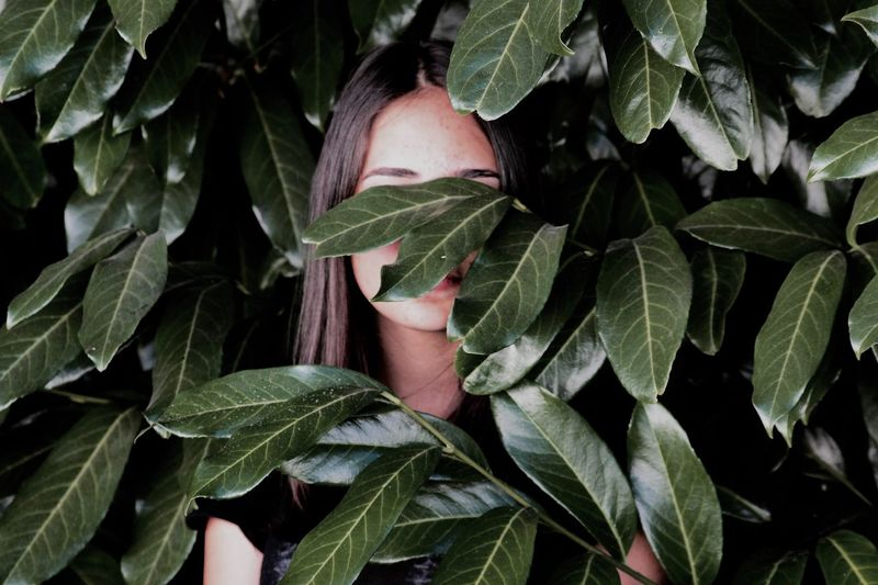 Close-up of woman hiding behind leaves