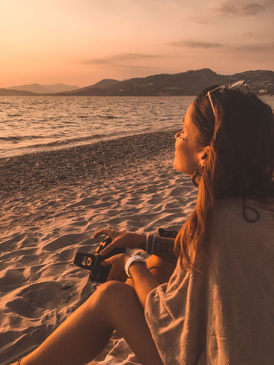 Woman relaxing on beach against sky during sunset