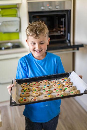 Smiling boy holding baking tray