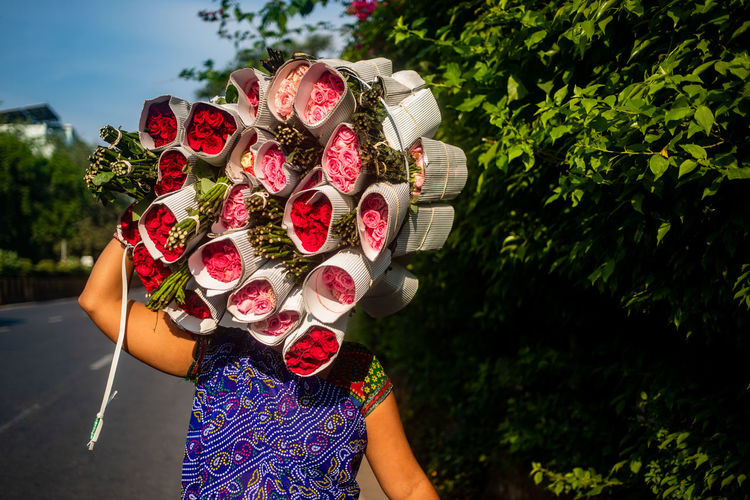 Midsection of woman holding bouquet of red rose