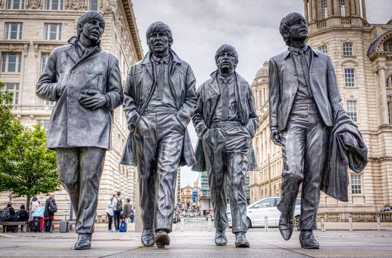 Statue of people walking on street in city