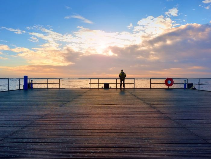 Silhouette man on pier over sea against sky during sunset