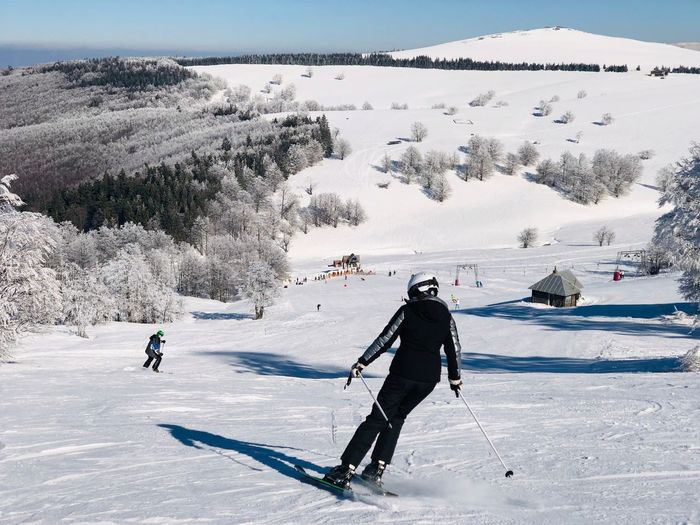 Skiers going down the slope with view of snowcapped mountains ahead on a day with clear blue sky Trees Forest Activity Landscape Resort Sunny Blue Sky Outdoors Motion Slope Skier Winter Snow Cold Temperature Winter Sport Mountain Sport Leisure Activity Ski-wear Ski Holiday Skiing Sports Equipment Adventure Extreme Sports Nature Mountain Range Beauty In Nature People Vacations Travel Destinations