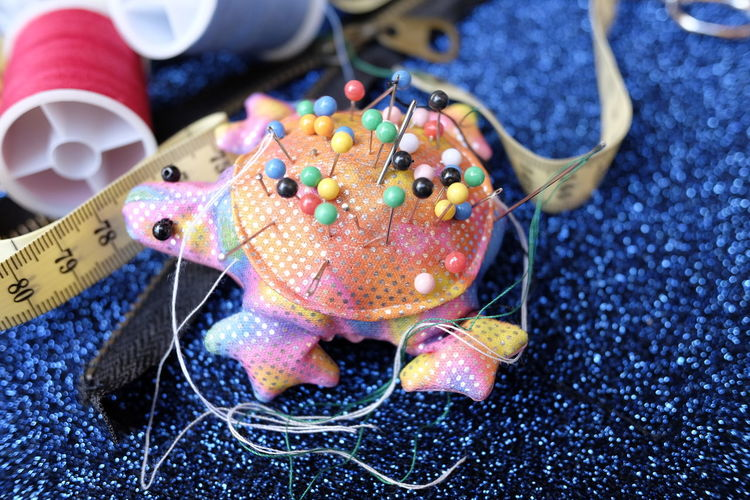 Close-up of pin cushion on fabric