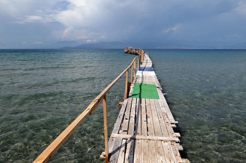 Jetty over sea against sky