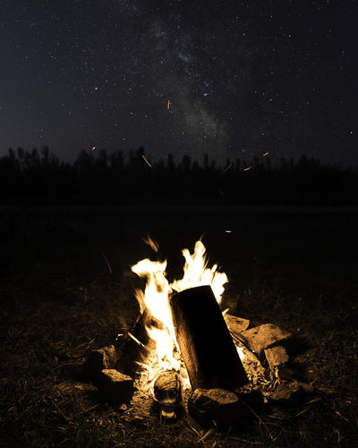 Bonfire on wooden structure in lake against sky at night