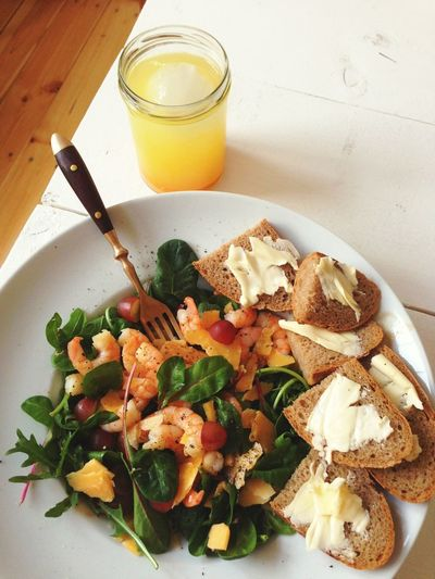 High angle view of prawns salad and juice on table
