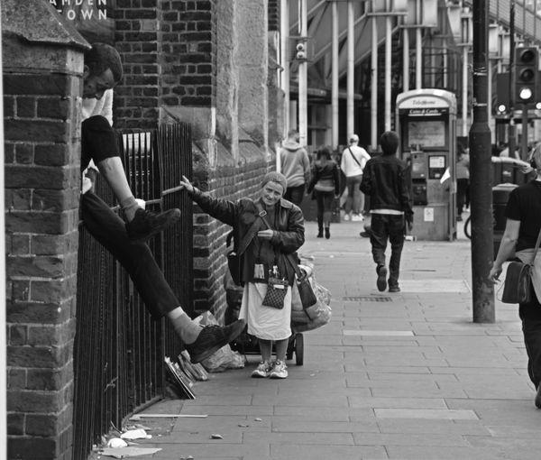 People walking on footpath by building