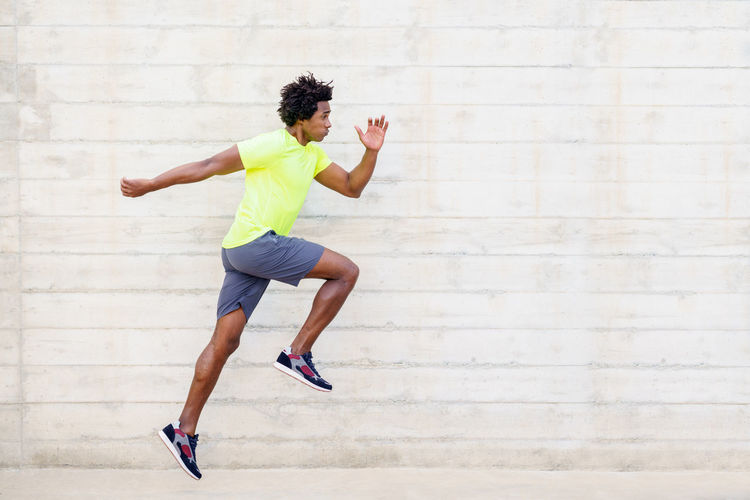Full length of young man running against wall