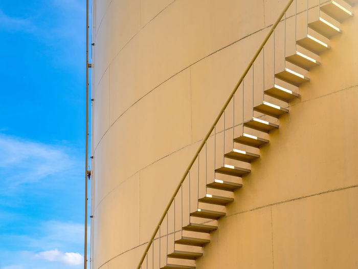 Low Angle View Of Steps On Silo Against Blue Sky