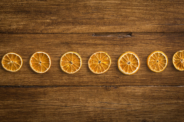 Dried orange slices in a row on a wooden table Fruit In A Row Table Orange SLICE Dried Festive Seasonal Christmas Ornament Wellbeing Wooden Backgrounds Recipe Citrus Fruit Food Directly Above Celebration Holiday Halloween Decorative Decoration Rustic Close-up Wood Grain