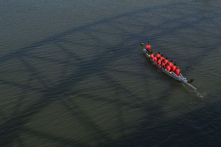 High angle view of people sitting on rowboat in river