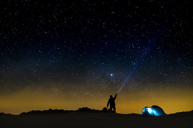 Silhouette man with flashlight against star field at night
