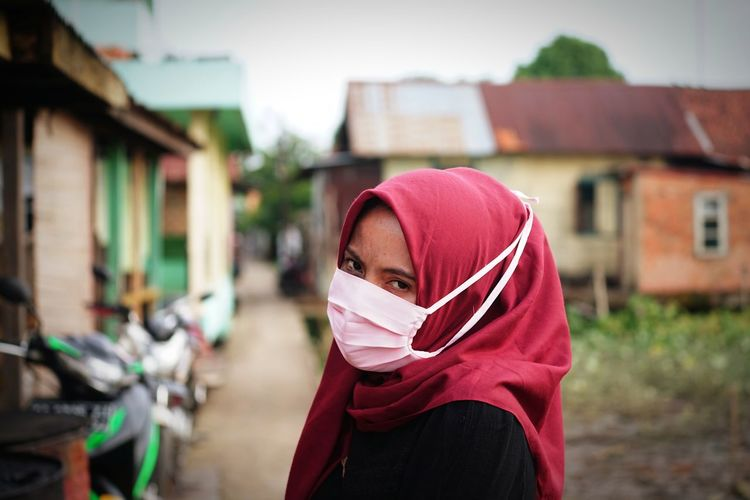 Portrait of young woman wearing mask against built structure