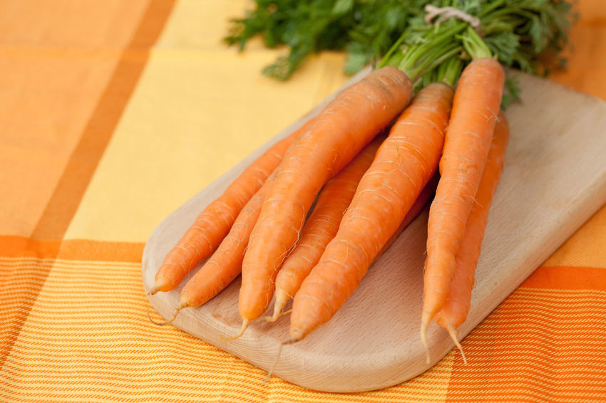 Bunch of fresh carrots on a cutting board Bunch Carrot Close-up Cutting Board Cutting Boards Day Food Food And Drink Freshness Healthy Eating Healthy Eating; Indoors  Kitchen Leaf Many No People Orange Color Raw Food Ready-to-eat Still Life Table Tablecloth Vegetable
