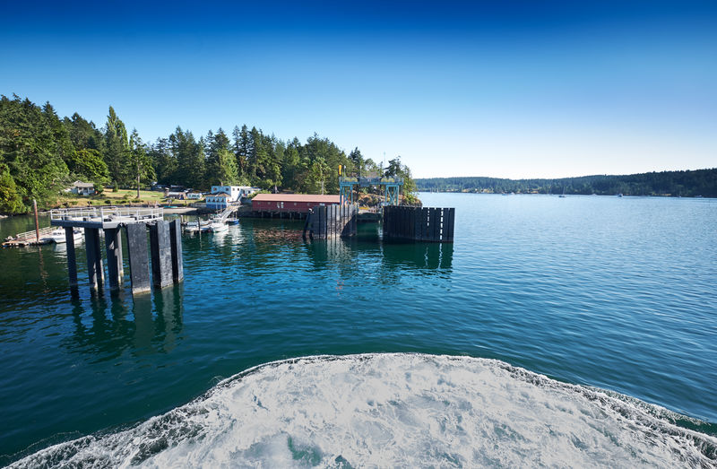 Ferry approaching the dock on Shaw Island, San Juan Islands, Washington Pacific Northwest  San Juan Islands Shaw Island Architecture Beauty In Nature Clear Sky Day Lake Nature Nautical Vessel No People Non-urban Scene Outdoors Plant Reflection Scenics - Nature Sky Tranquil Scene Tranquility Transportation Tree Water Waterfront
