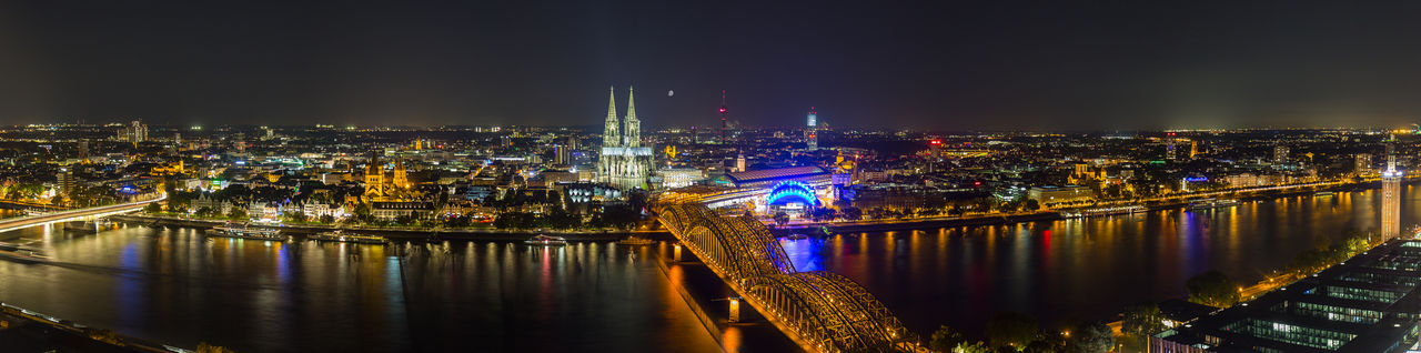 Cologne Skyline panorama with Cathedral at night Cathedral Cityscape Cologne Exploring German Lights Panorama Panoramic View Reflection Rhine Skyline Aerial View Cityscapes Cologne Cathedral Colognecathedral Hohenzollernbrücke Illuminated Landmark Night Rhine River Travel Destinations