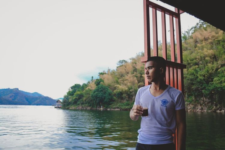 Man having drink while standing by lake