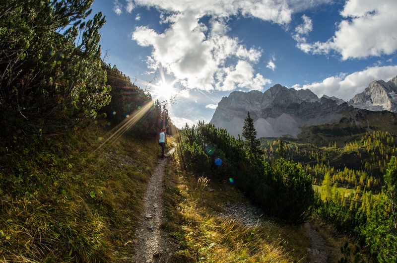 Dirt road passing through mountains against cloudy sky