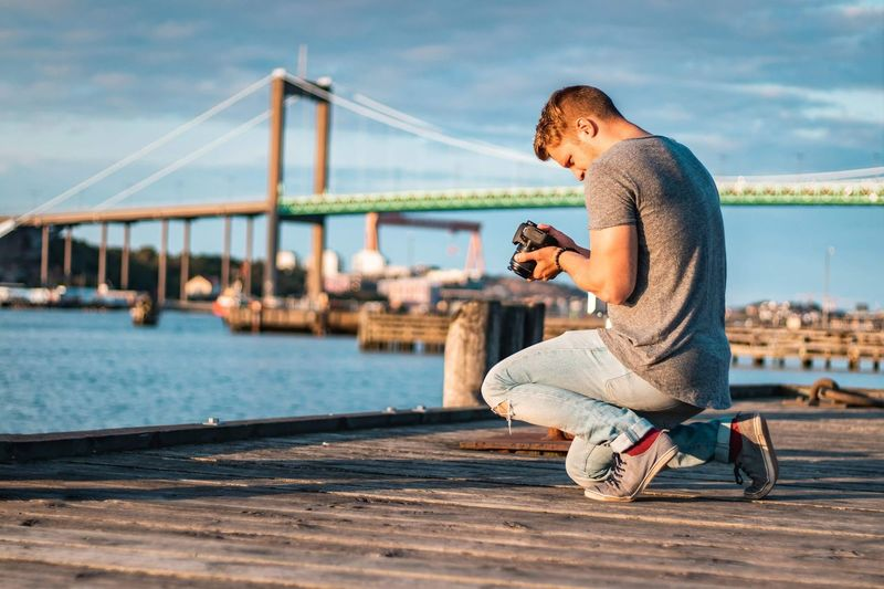 Man Holding Camera On Pier By Bridge Over Sea