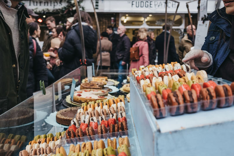 Unidentifies people buying colorful macaroons a market stall at greenwich market, london, uk.
