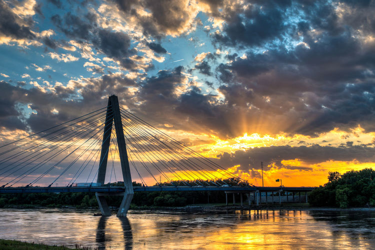 Christopher s bond bridge over missouri river against cloudy sky at sunset