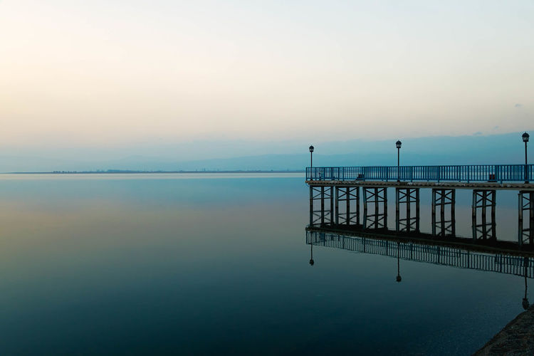 Wonderful reflections on Lake Iznik as the sun was setting. Calm, Composed, Tranquil, Peaceful, Untroubled, Relaxed, At Ease, Unperturbed, Unruffled, Unworried; Placid, Equable, Centered Image, Mirror Image, Likeness, Reflection, Reflect, Pond, Pool, Tarn, Reservoir, Slough, Lagoon, Water, Waterhole, Watering Hole, Inland Sea Sundown, Nightfall, Close Of Day, Twilight, Dusk, Evening Support, Cutwater, Pile, Piling, Abutment, Buttress, Stanchion, Prop, Stay, Upright, Pillar, Post, Column, Wood, Lights, Plank, Timber, Blue, Sky, Heaven, Clouds, Atmosphere, Colorful, Azure, Jetty, Quay, Wharf, Dock, Levee, Landing, Landing Stage Lake, Iznik, Turkey, Water, Middle East, Asia, Antolia, Ottoman, Mist, Background, Smooth, Environment, Backdrop, Scene, Trip, Excursion, Journey, Tour, Tourist, Visit, Vacation, Get -away, Holiday,