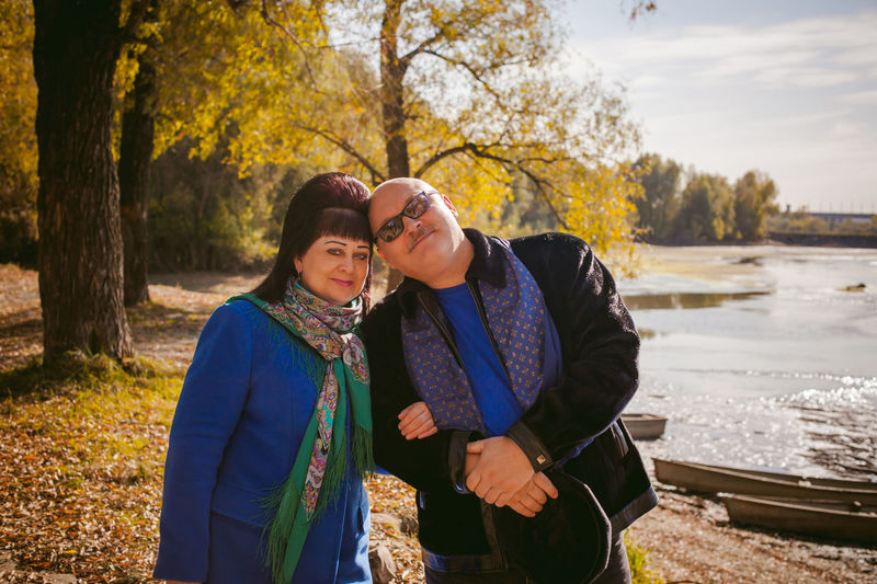 Portrait of mature couple standing in forest by lake during autumn