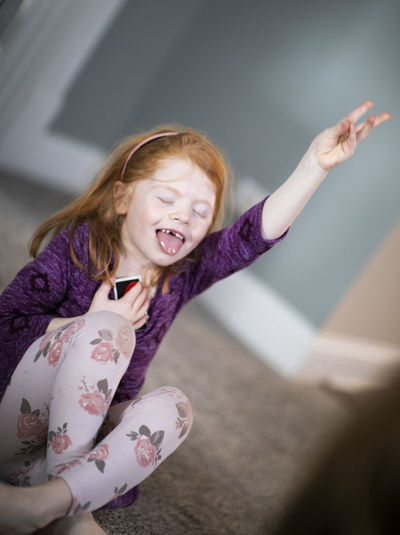 A five-year-old girl celebrates after winning a card game. Childhood Child Happiness Smiling Girls Cheerful Emotion Females Women Indoors  Portrait Offspring One Person Looking At Camera Limb Human Arm Human Body Part Hair Human Limb Arms Raised Mouth Open Positive Emotion Innocence Hairstyle Joyful