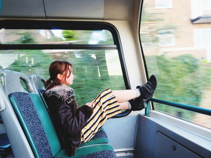 Side view of girl sitting in train