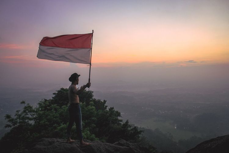 Flag standing on mountain against sky during sunset