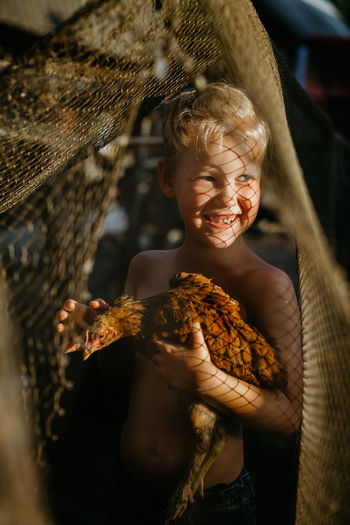 Smiling shirtless boy holding chicken while standing outdoors