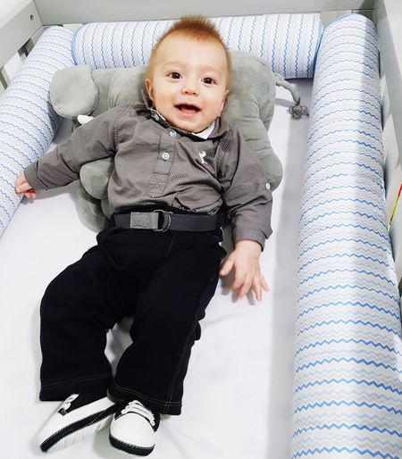 High Angle View Of Smiling Baby Boy Lying On Bed