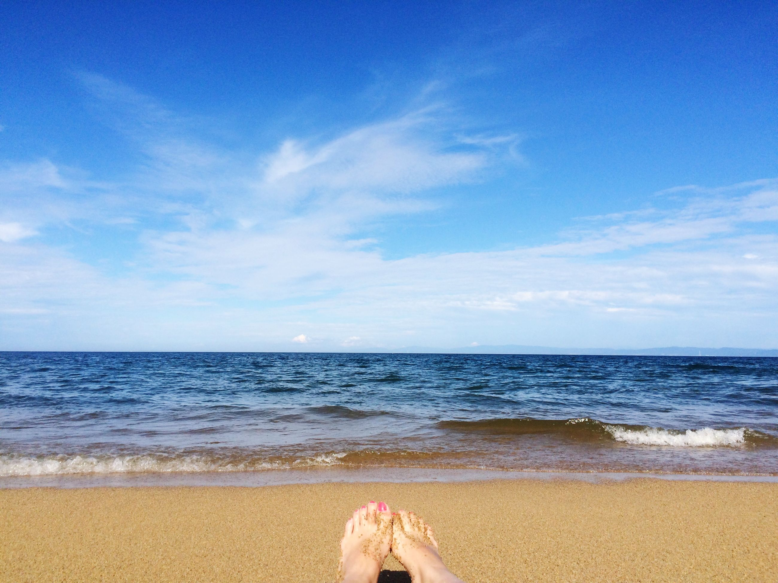 sea, beach, horizon over water, water, sand, shore, sky, person, low section, barefoot, vacations, personal perspective, scenics, leisure activity, beauty in nature, lifestyles, tranquil scene