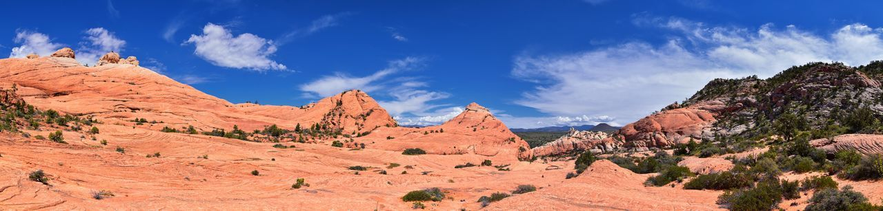 Panoramic view of rocky mountains against blue sky