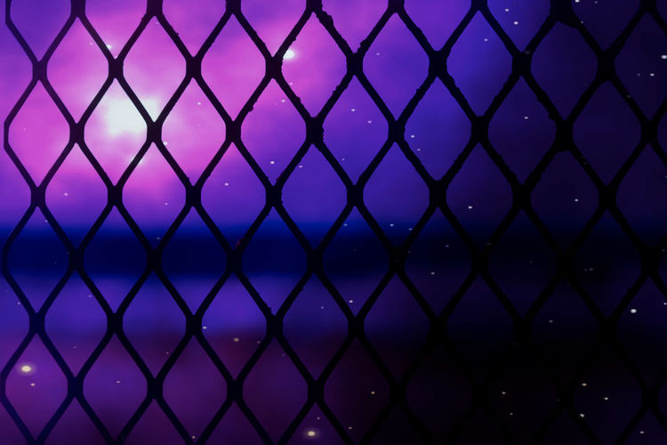 Close-up of chainlink fence against blue sky
