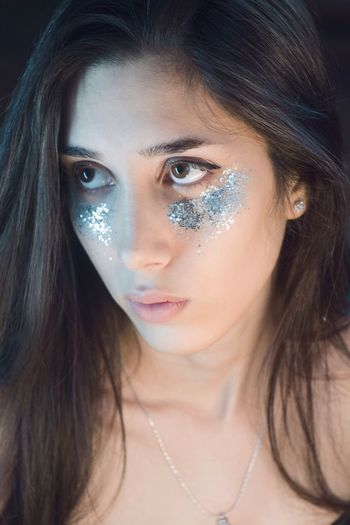 Young woman with silver shimmer on face