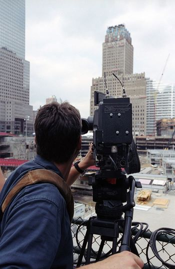 Rear View Of Man Photographing With Movie Camera Against Buildings