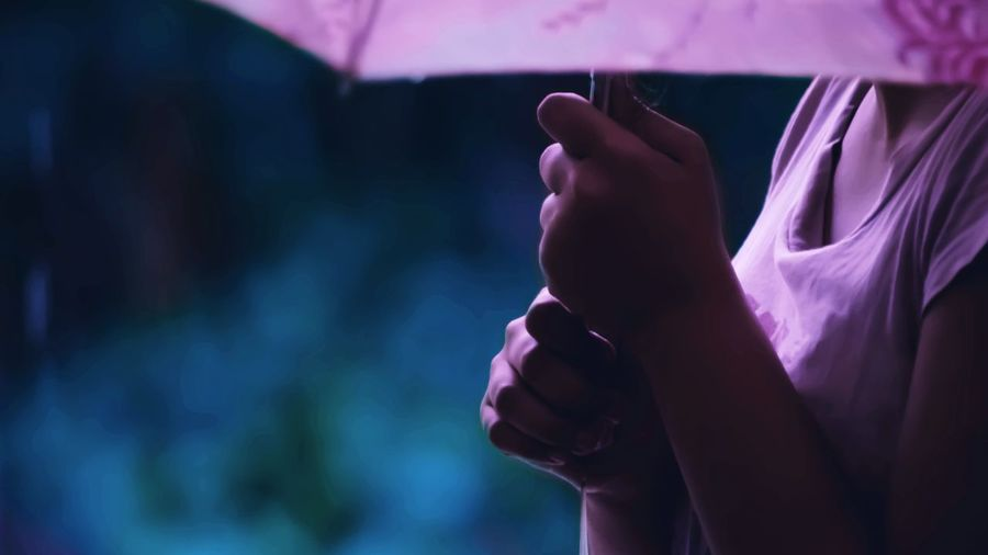 Cropped image of woman holding umbrella during rainy season