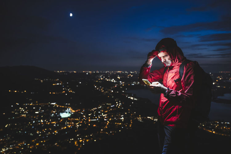 Woman standing by illuminated cityscape against sky at night
